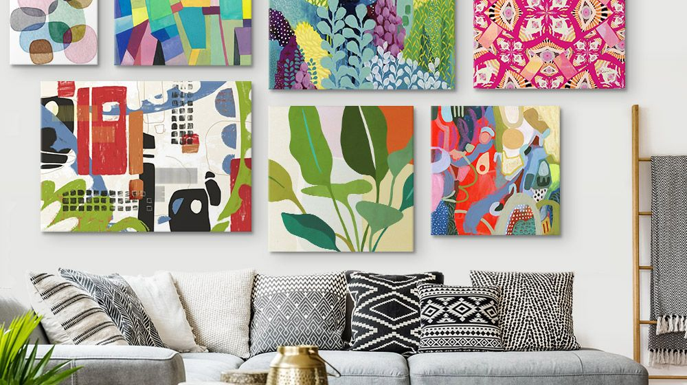 Gallery wall of vibrant canvas prints in over a couch in a Bohemian-styled Living Room