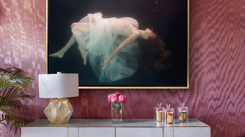 Surreal photographic canvas print of woman underwater hung in a richly decorated room with metallic accents