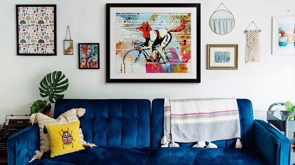 Fox riding a bike framed art print in a wall display over a colorful living room couch.