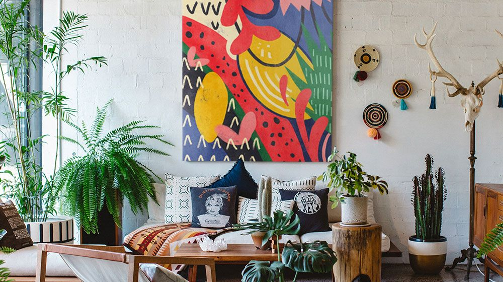 Vibrant Maximalism canvas wall art in a bright, plant-filled living room interior.
