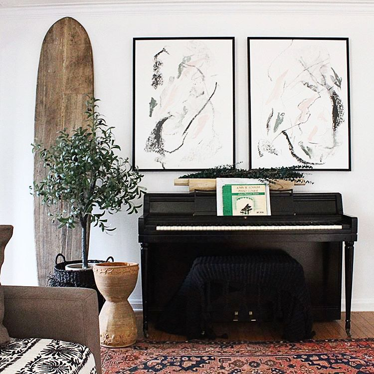 Pair of two abstract line art canvases with black frame over a piano in eclectic living room