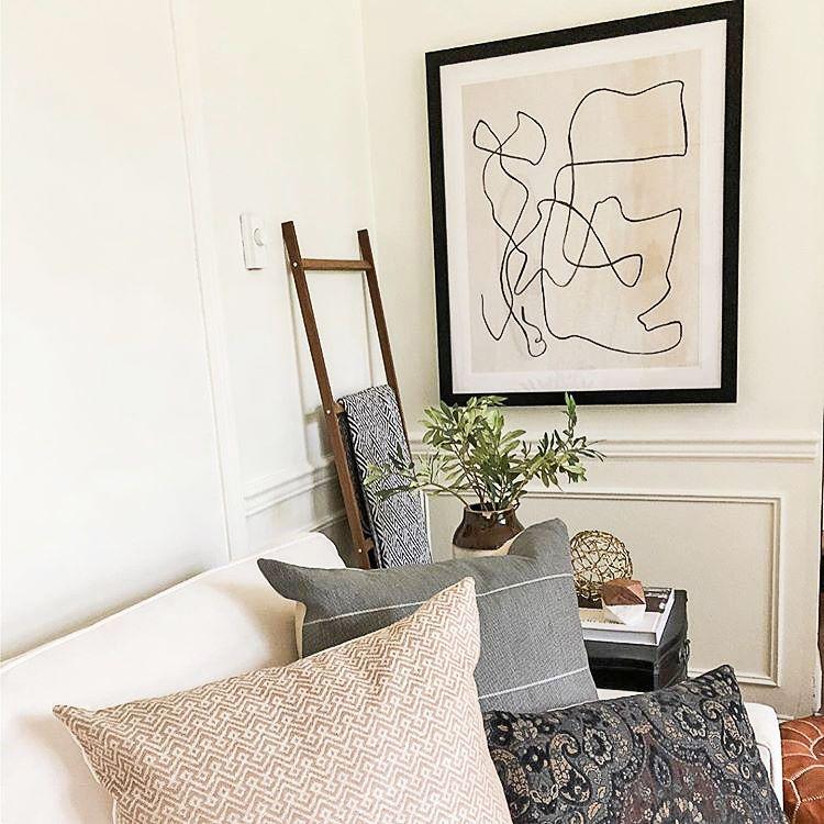 Bold line art print in black frame in a cozy living room.