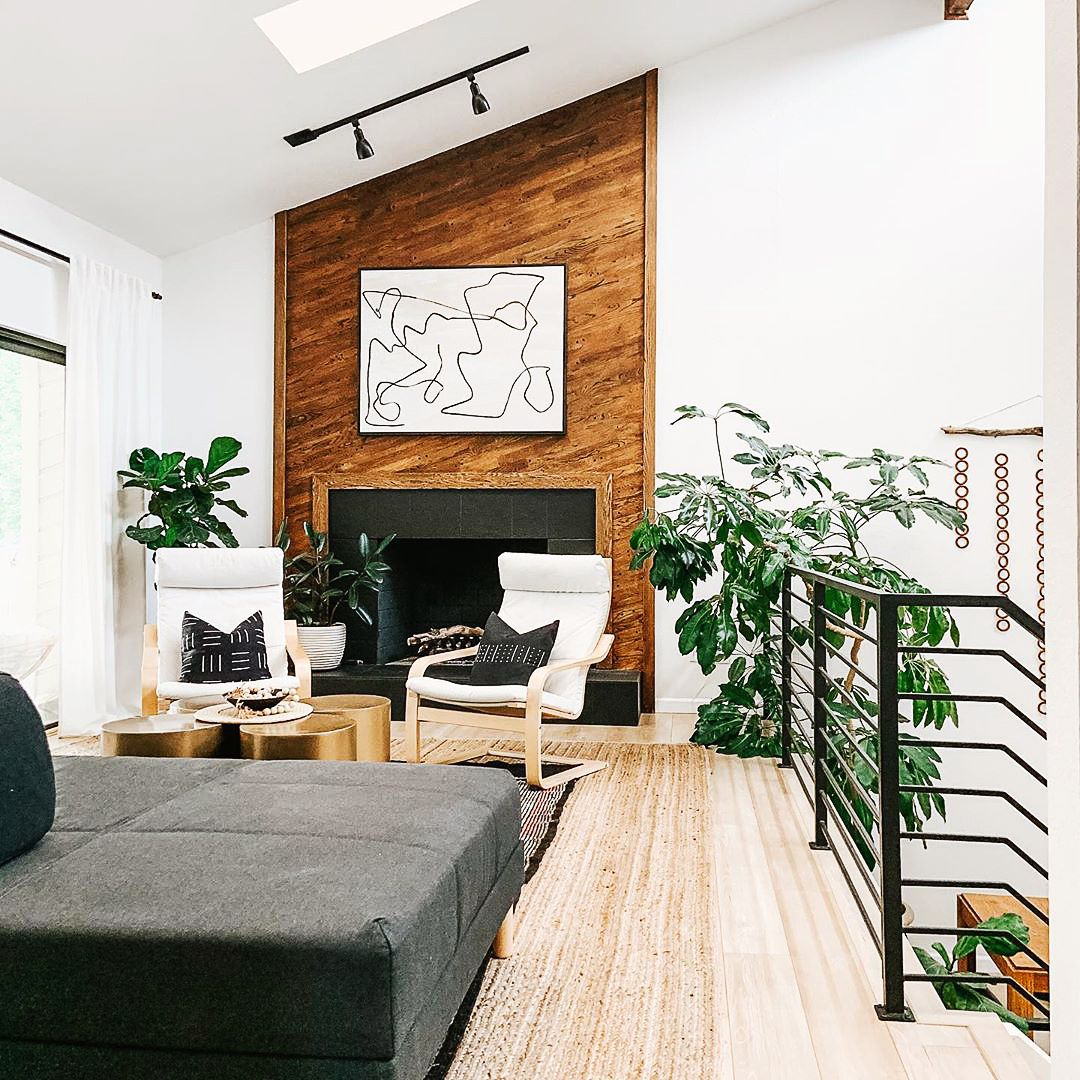 Bold line art canvas print in black floating frame over fireplace in contemporary living room.