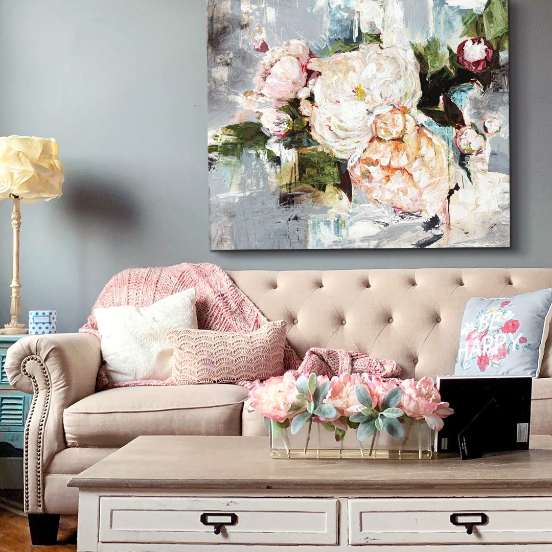 Pink and gray peony abstract painting above light pink couch with rustic wood table.