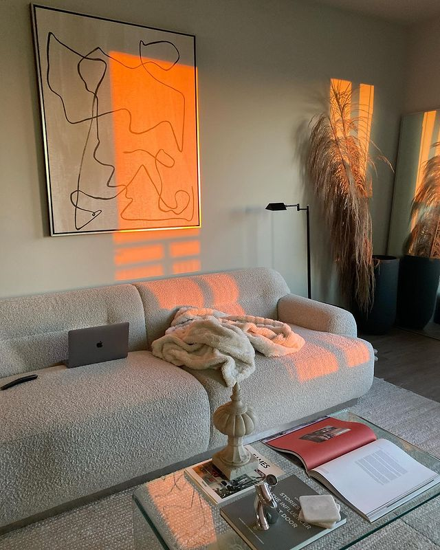 Bold line art canvas print in silver float frame in living room at sunset.