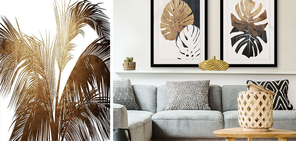 Two gold and black Monstera plant art prints in black frames over a gray couch.