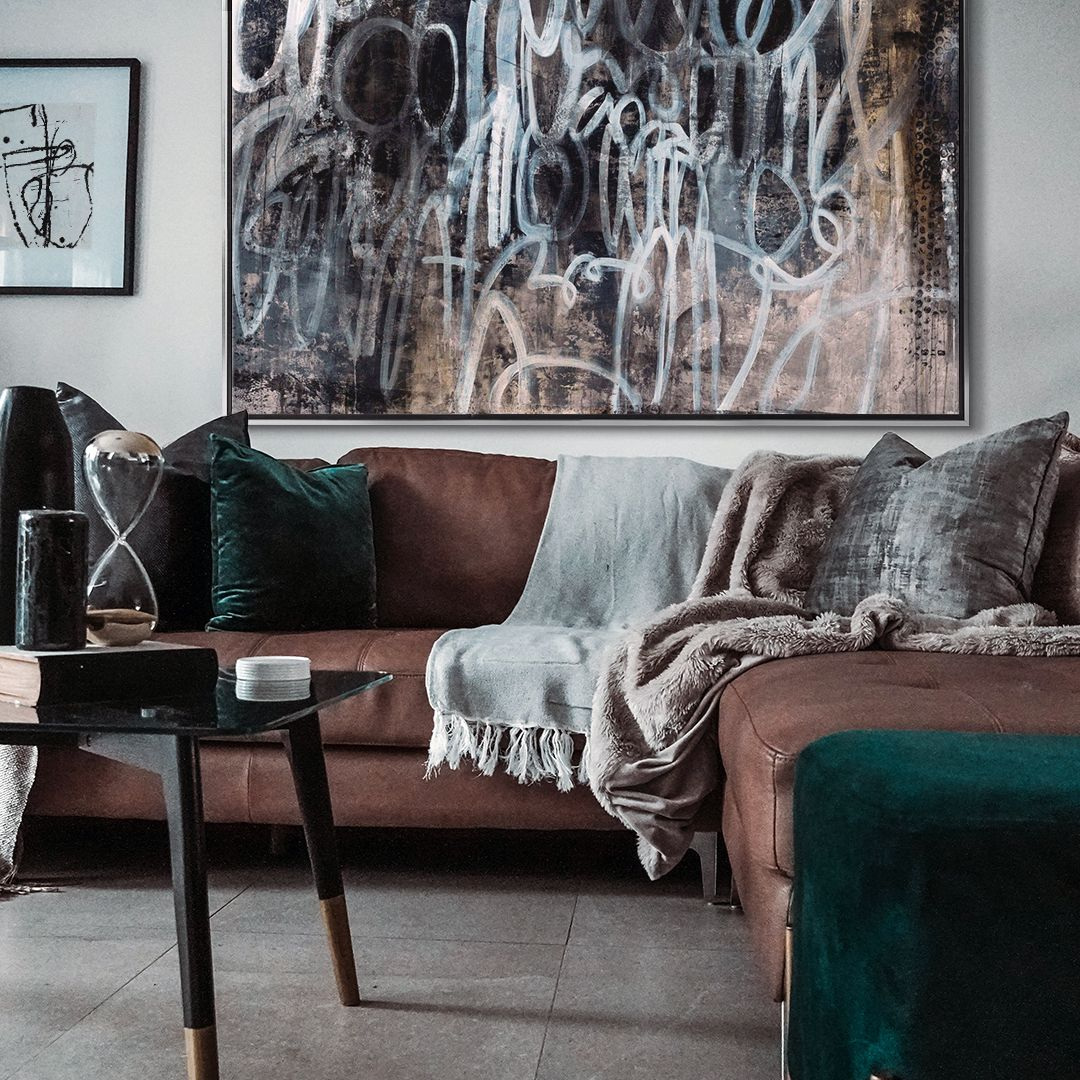 Large contemporary abstract print in silver floating frame over a cozy couch in neutral living room.