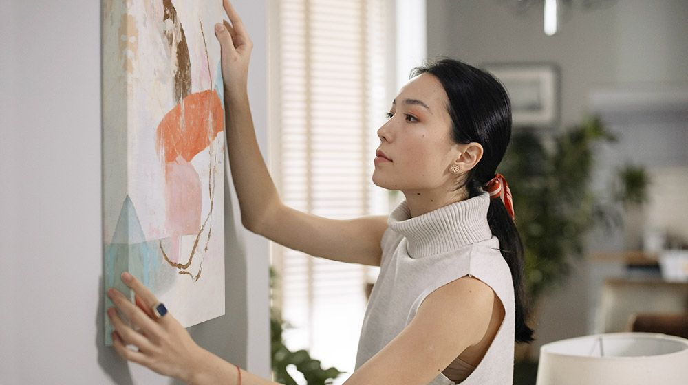A woman hanging a canvas art print on the wall in her home.