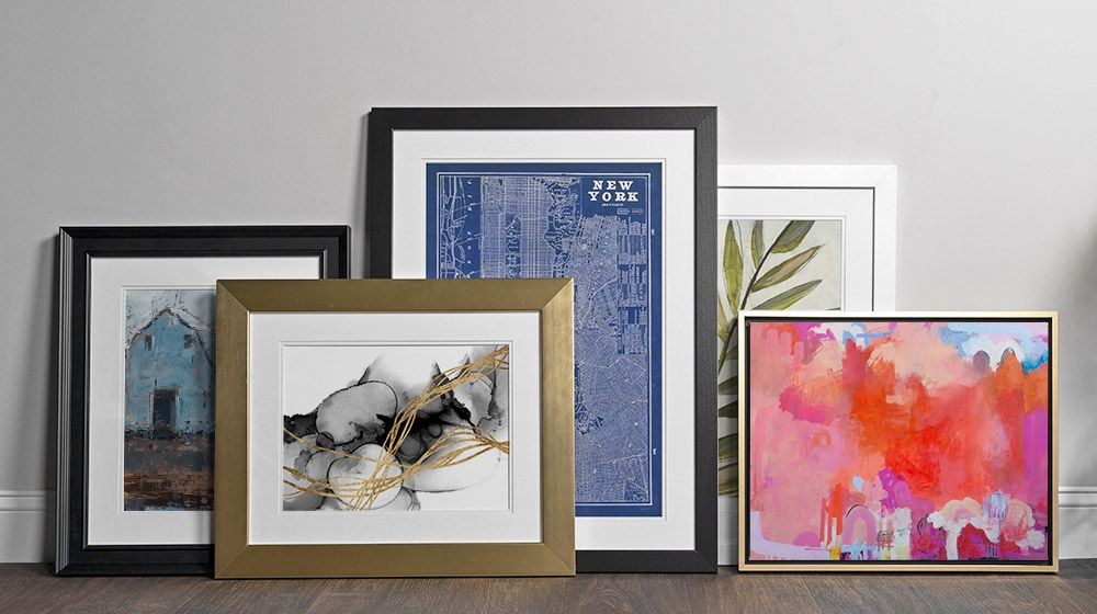 An assortment of framed art products leaning against a wall.