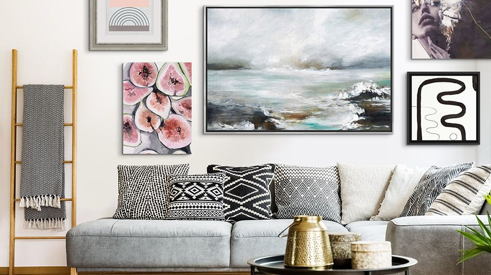 A wall display of a variety of canvas prints and framed art in a living room.