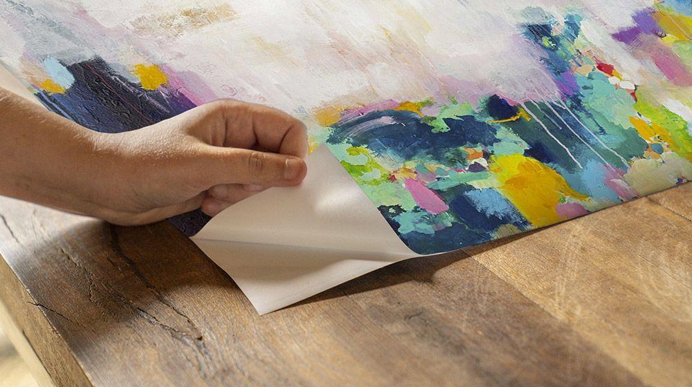 A woman preparing to hang an abstract art wall peel.