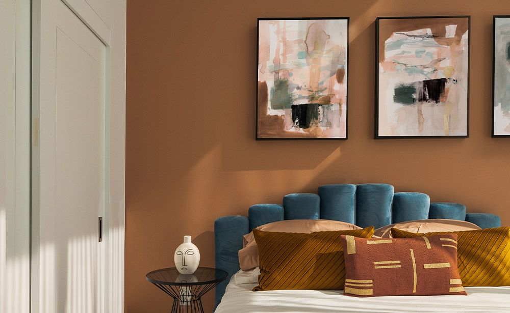bohemian bedroom with three abstract art canvas prints hanging above the bed on a tan-colored wall
