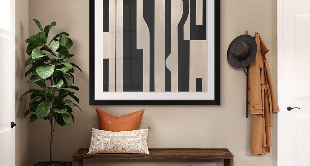Framed print featuring black and tan abstract art in a luxury entryway.