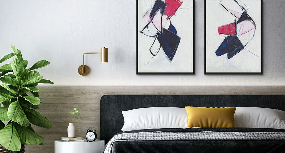 Two symmetrical abstract art prints in black floating frames over the headboard of a bed.
