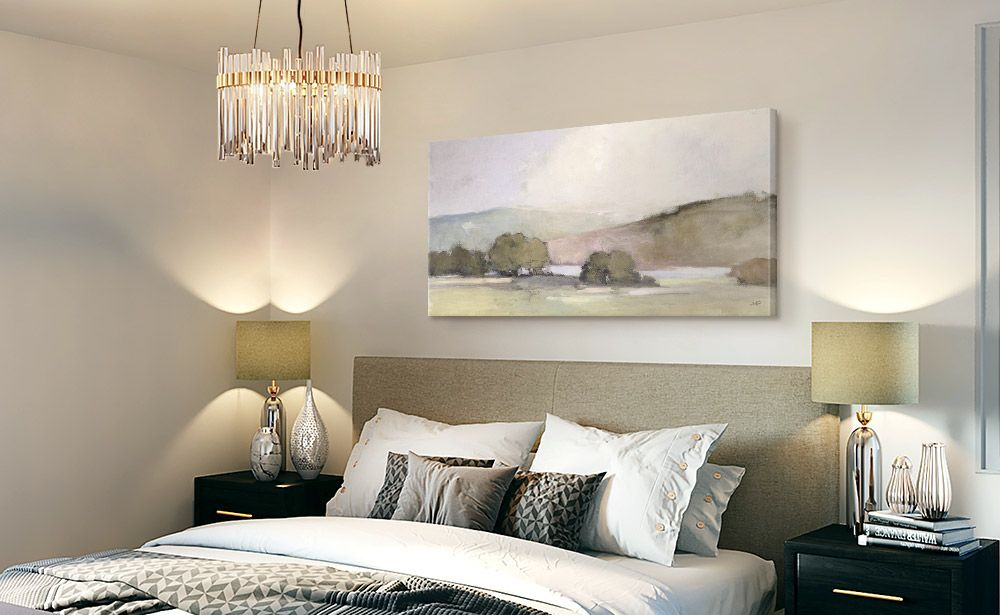 coastal canvas art print hanging above a bed in bedroom with chandelier